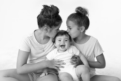 sisters kissing baby sister