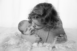 Daughter kissing baby brother