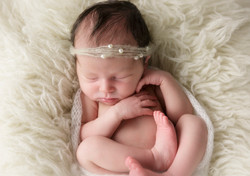 newborn girl curled up