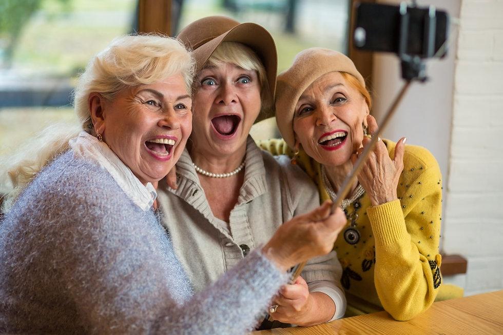 Women taking selfie at table. Three seni