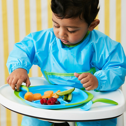 Child eating from a plate in a B.Box Smock Bib in colour Ocean Breeze