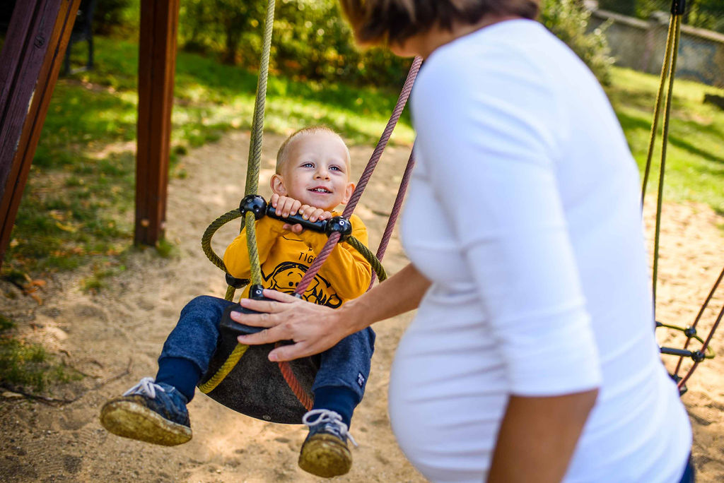 Mom playing with her son on the swing