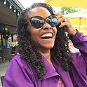 A black woman with a purple top and stylish sunglasses. She is lauging or smiling with an open mouth and with one hand she is brushing her hair over her ear.