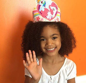 """A young black girl wearing a paper birthday tiara, smiling, and with hand up to wave """"hello"""""""