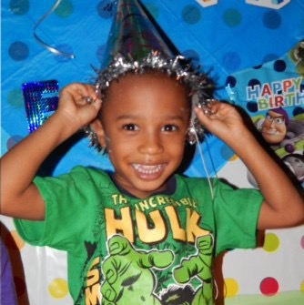 Young black boy wearing Incredible Hulk t-shirt and putting on a party hat with a big smile