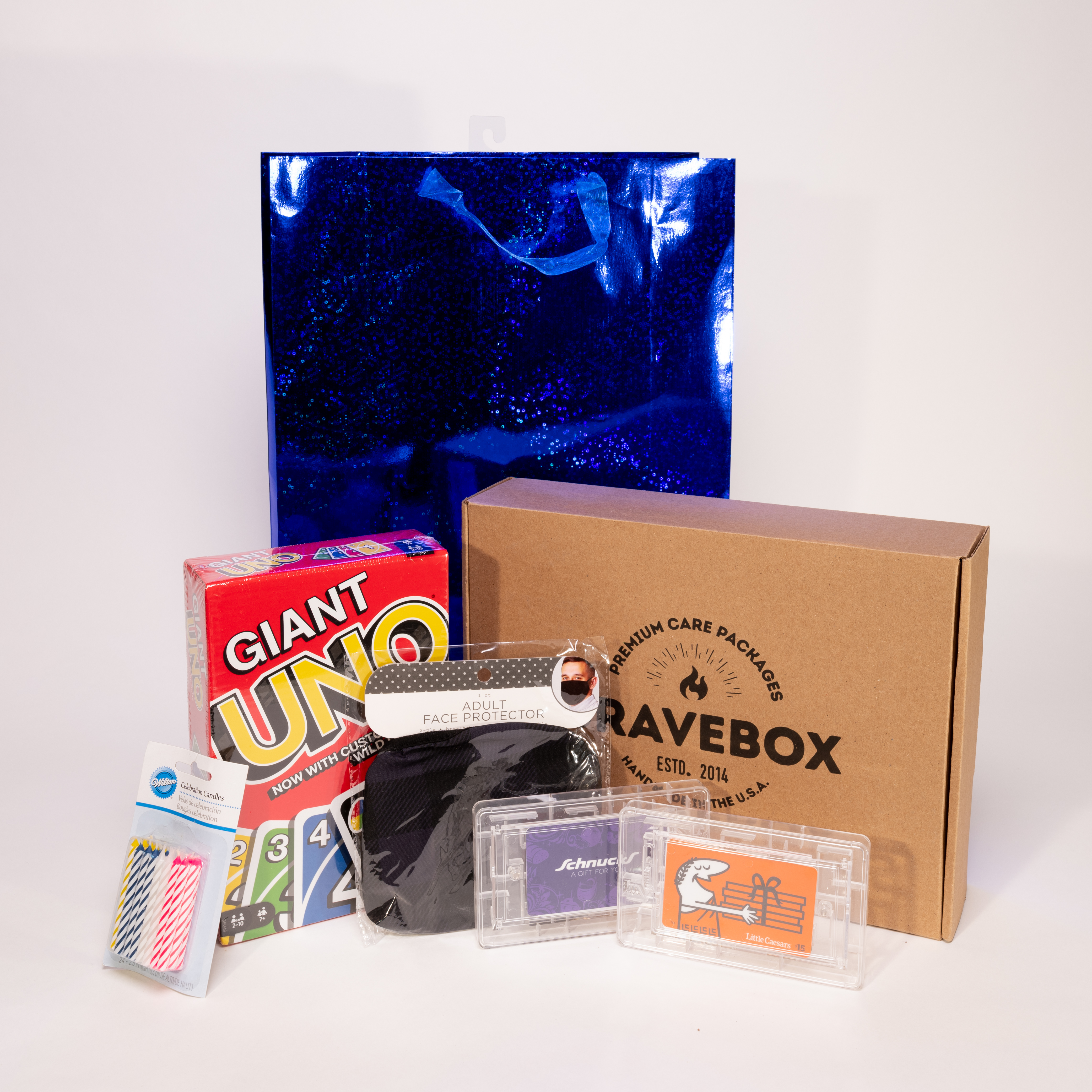 """A staged photoshoot image of the contents of a """"birthday box,"""" including the card game UNO and some"""
