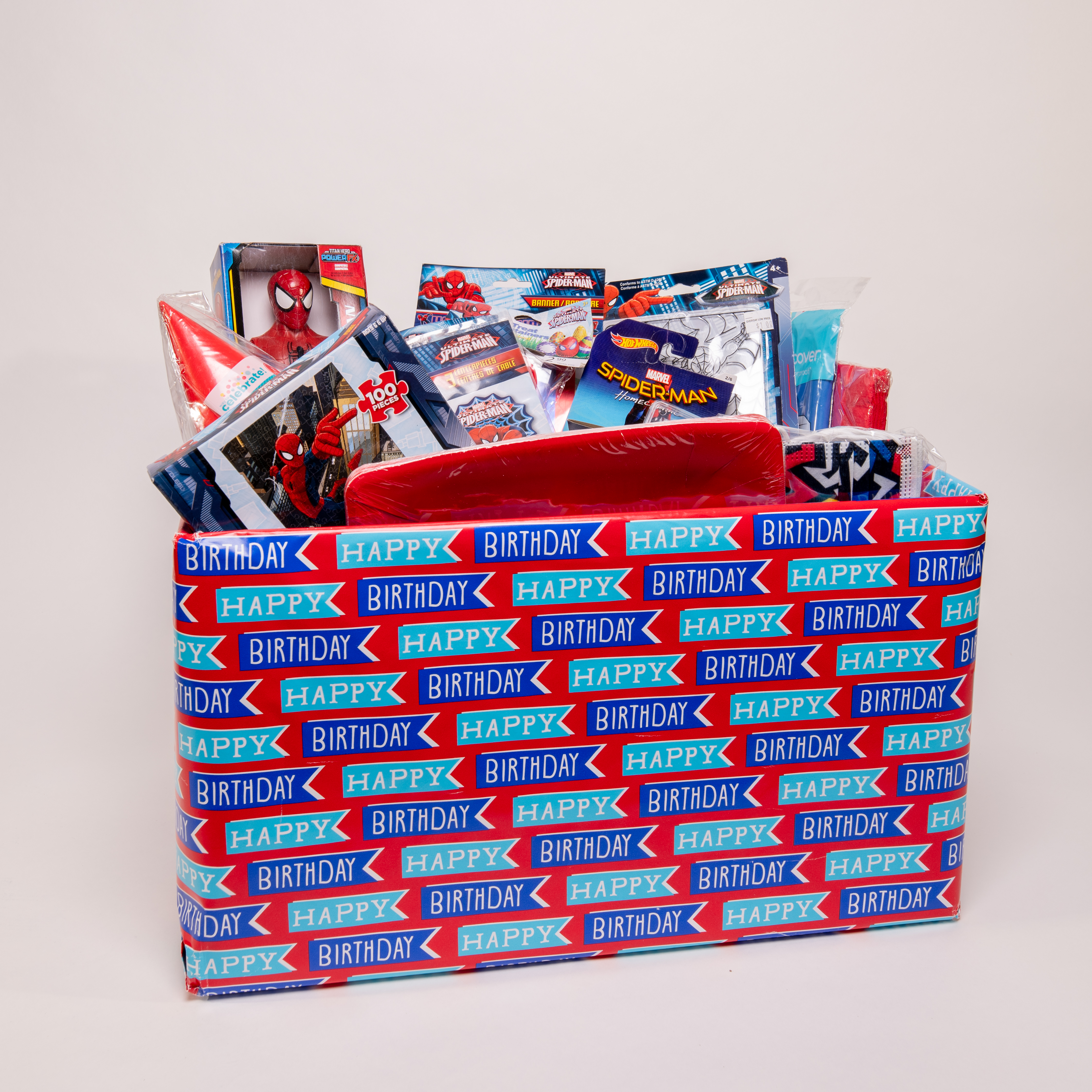 """A staged photoshoot image of a """"birthday box"""" package, including Spiderman action figure and toys"""