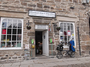 Blanchland, post offcie and shop, Northumberland, with Brompton bicycle carrying camping gear