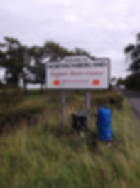 Northumberland, Border country, sign, with loaded Brompton bicycle carrying camping gear