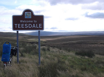 Teesdale sign with view of upper Teesdale and loaded Brompton Bicycle carryin camping gear
