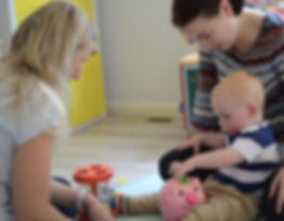 Two adults watching over toddler learning hand skills