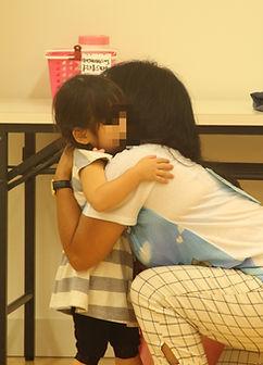 グッバイのハグをする女の子と講師