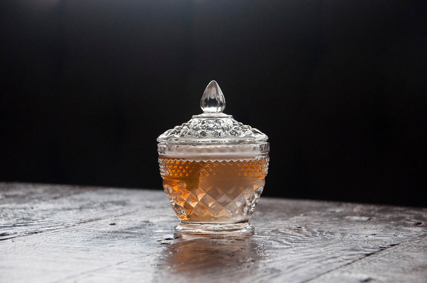 Smoked Cocktail sealed in vintage glass jar on wook table iwht dark background