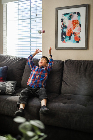Boy throwing toy in the air on sofa | Las Vegas family photographer
