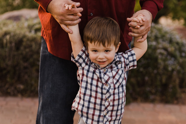 Toddler son holding hands with Dad