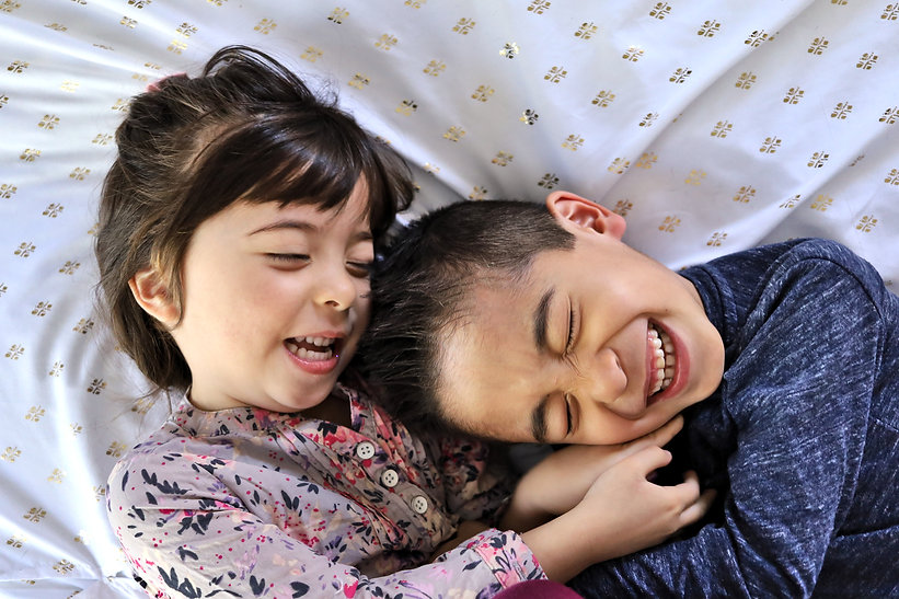 Sister tickling brother on bed | In home lifestyle family photography in Las Vegas, NV by Jennifer Hyman Photography