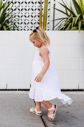 Toddler girl dressed in flowing white dress walks downtown
