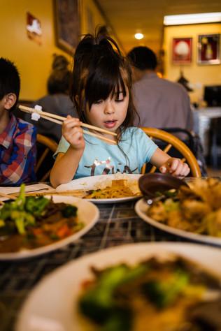 Girl using chopsticks in restaurant