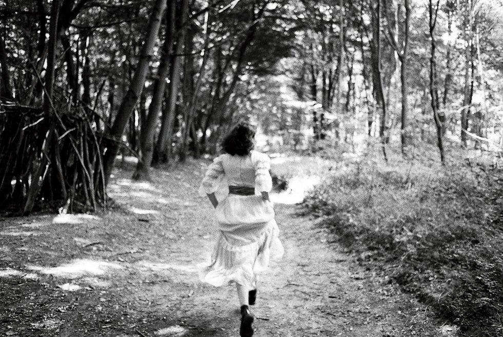 Jeune femme qui court dans les bois , prise avec une pellicule photo noir et blanc.