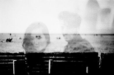 Un couple sur une plage en noir et blanc, la photographie a été prise avec une pellicule photo.