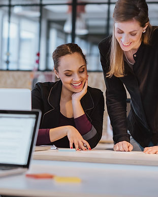 two-young-woman-at-office-working-on-a-n