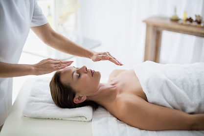 midsection-therapist-performing-reiki-wo