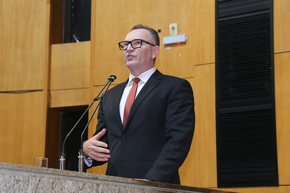 #PraCegoVer: foto deputado estadual Sergio Majeski discursando no Plenário da Assembleia. Homem branco, alto, com  óculos. Fundo painel de madeira.