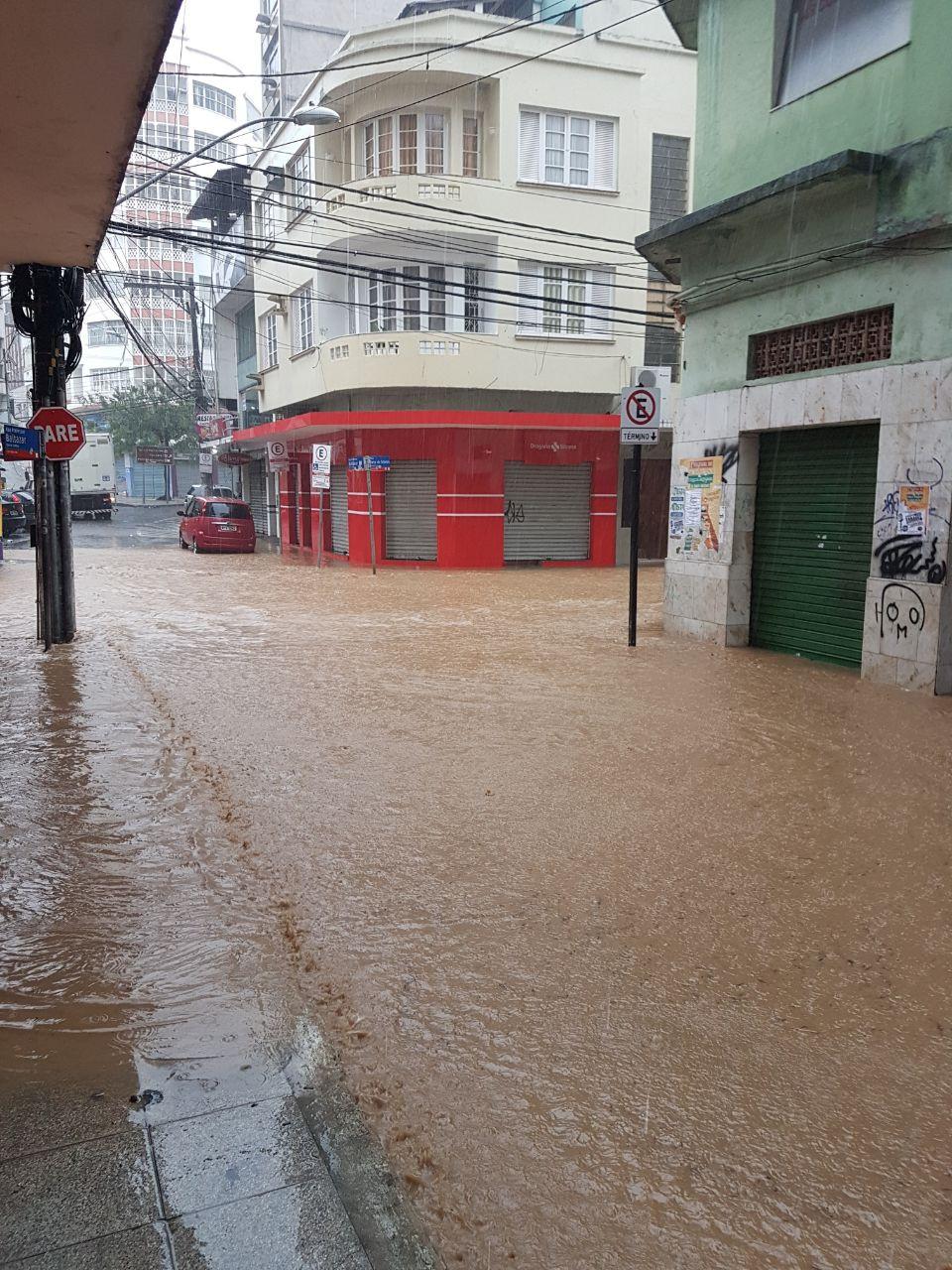 #PraCegoVer: Rua 7, Vitória, Espírito Santo. Rua com prédios e fachadas de loja, completamente alagada por água de chuva, enchente.