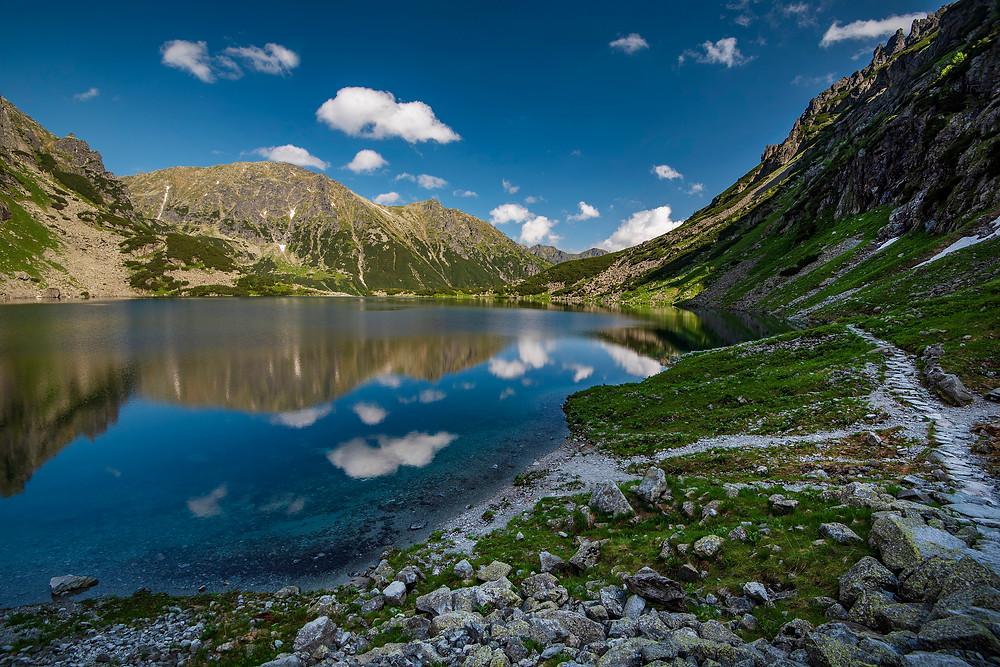 Tatranské pleso s čistou vodu s odrazom hôr a modrou oblohou