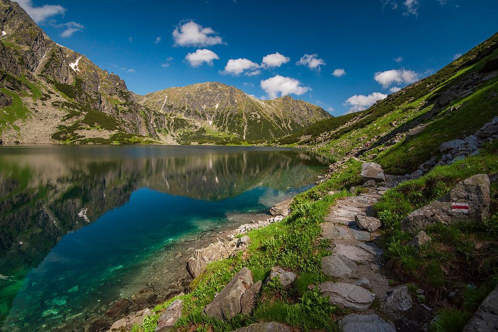 Chodník okolo jazera s odrazom hôr a modrou oblohou