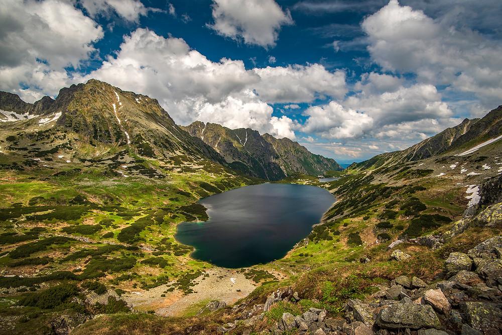 Dolina so zelenou trávou, horami a jazerom vo Vysokých Tatrách