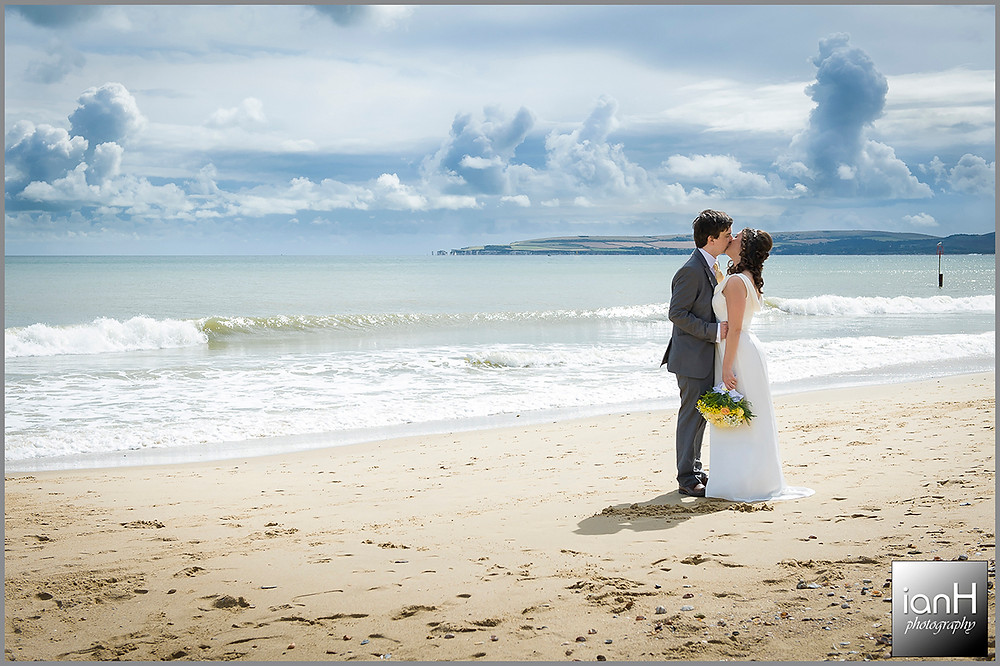 Bride and Groom kiss on Bournemouth beach with the Purbecks and Old Harry Rocks in the distance