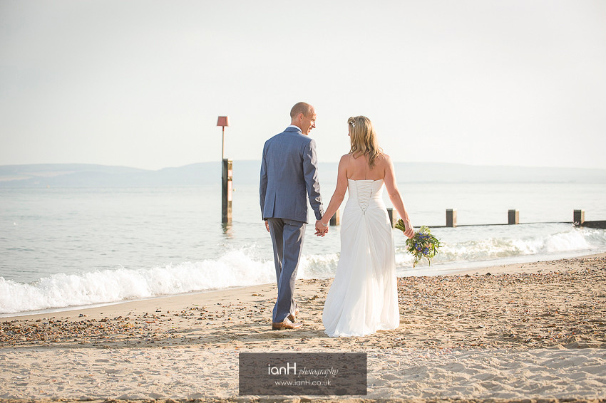 Bride and Groom walk hand in hand along Bournemouth beach at sunset