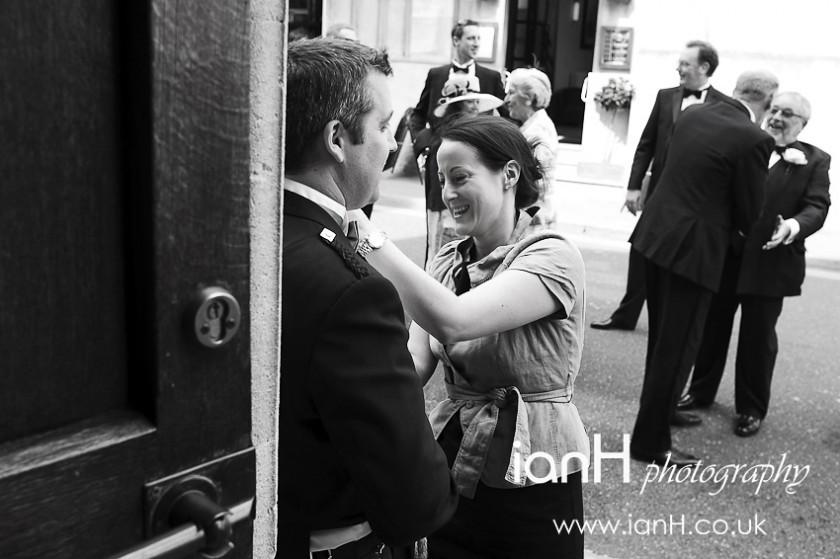 Wedding planner adjusts buttonhole of Usher at wedding