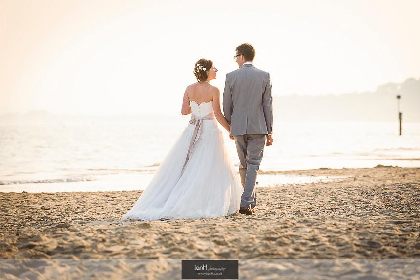 Bride and Groom walk along Bournemouth beach