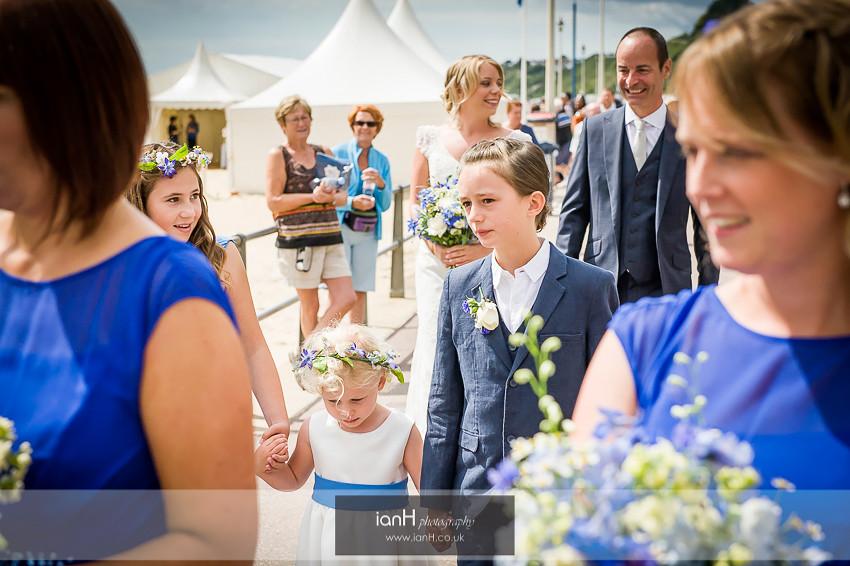 Flower-girls walking to a Bournemouth beach wedding