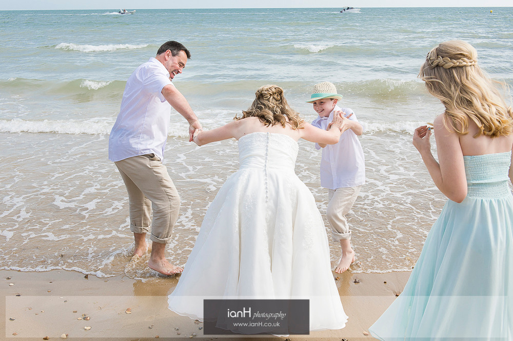 Bride and Groom paddling at Bournemouth beach wedding