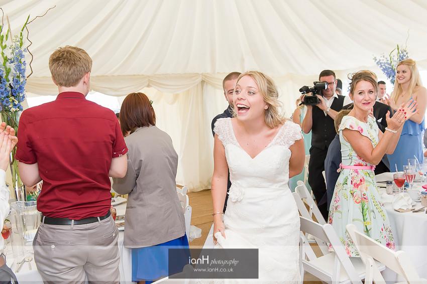 Bride's reaction as she enters her beach wedding reception