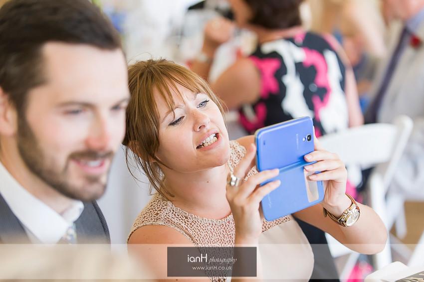 Guest using smartphone at beach wedding