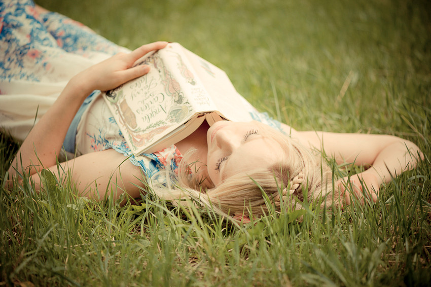 Beautiful blond girl laying down in the long grass