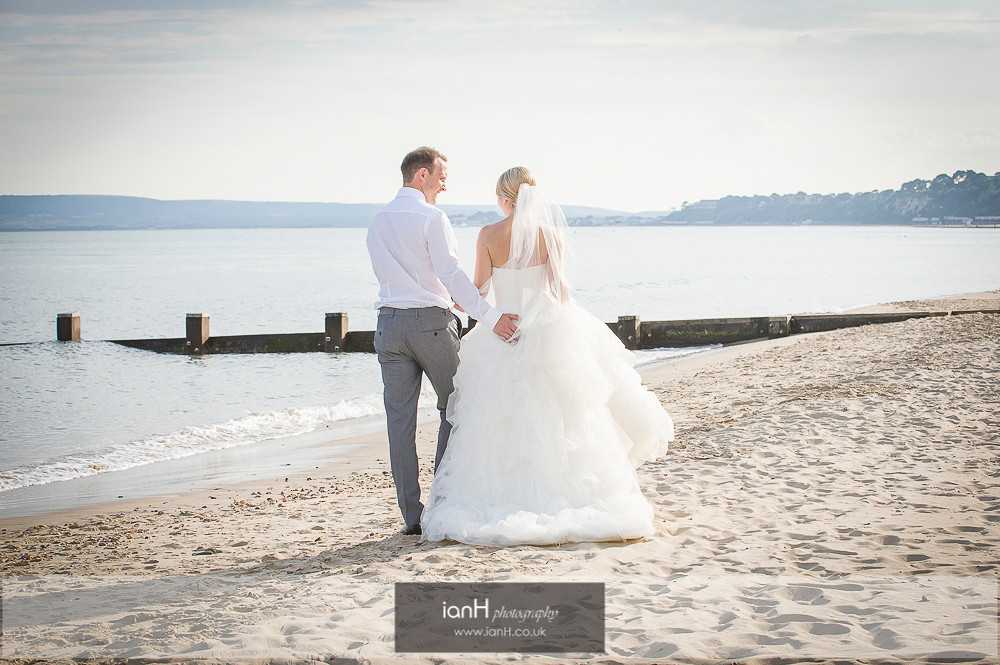 Bride and Groom walking along Bournemouth beach