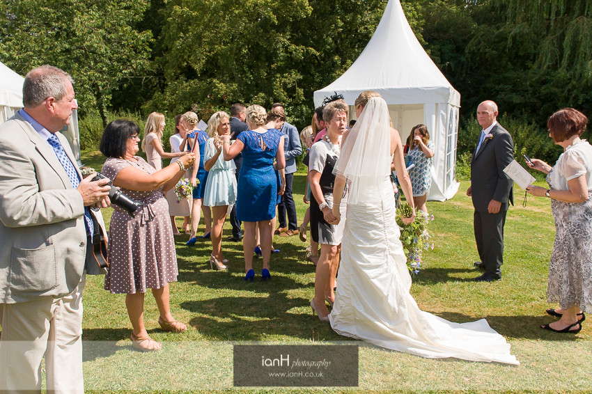 Guests photographing the Bride at a Hampshire country marquee wedding