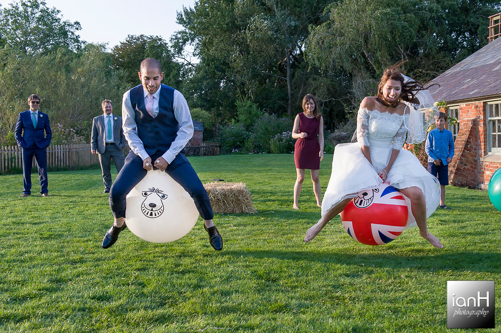 Bride and Groom in Spacehopper race at Sopley Mill Summer wedding