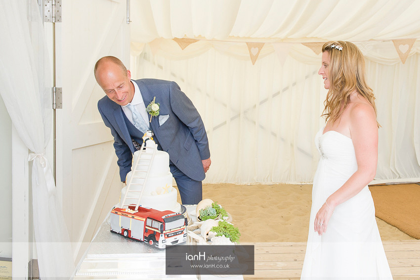 Bride and Groom inspecting their beach wedding cake