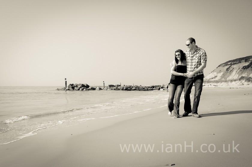 Engaged-couple-walking-along-beach