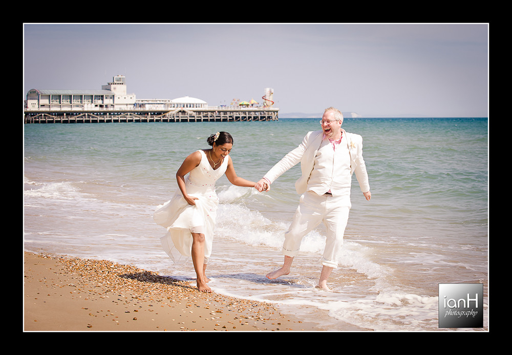Beach Weddings Bournemouth with the Bride and Groom enjoying a splash in the sea