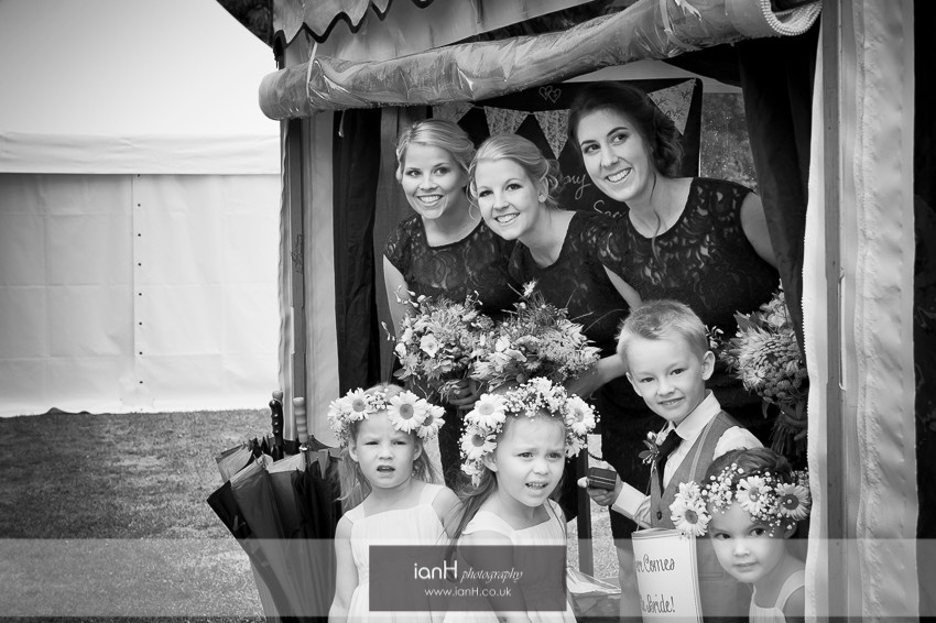 Bridesmaids and Flowergirls shelter as they wait for the Bride