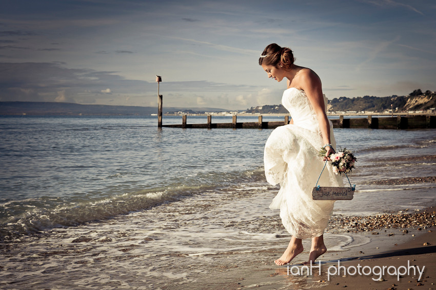 Beach_weddings_Bournemouth_bride_dipping_toes_in_the_sea photography