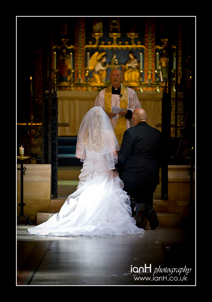 Bride and Groom kneel at the altar in a Bournemouth Church - Bournemouth wedding photographer