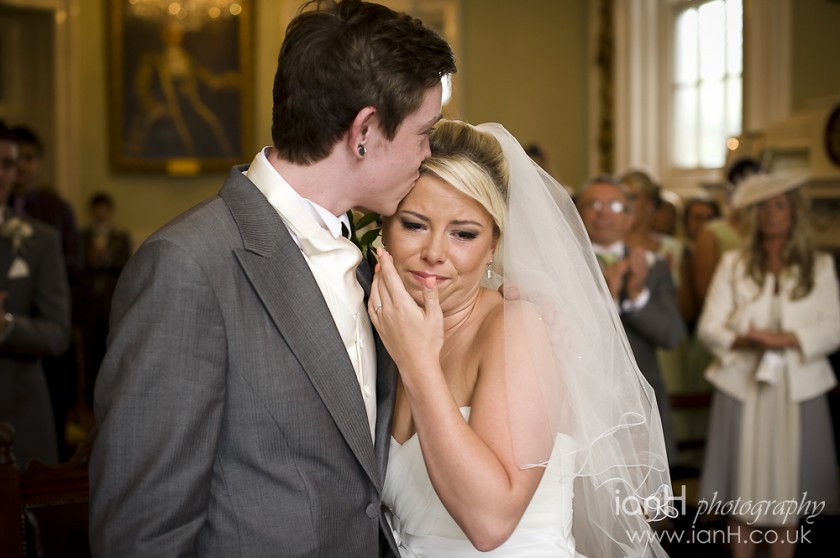 Groom_hugs_his_Bride_as_she_wipes_away_a_tear_at_their_wedding_in_Bournemouth_Town_Hall